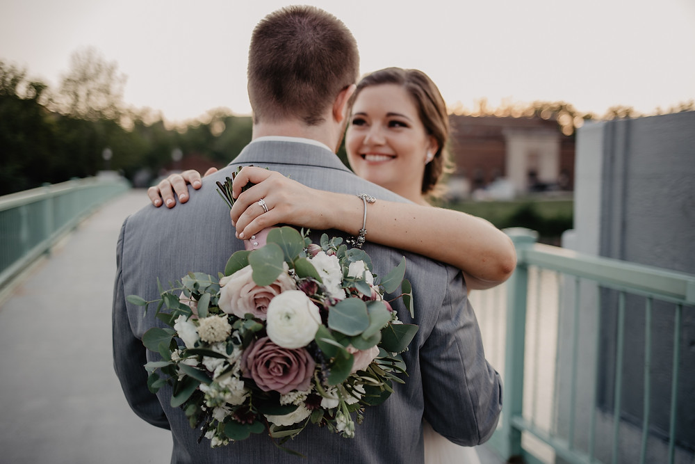 bride and groom hugging on bridge in iowa city with bridal bouquet of roses, ranunculus, and eucalyptus by studio bloom