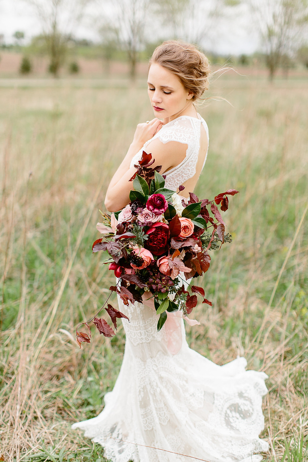 bride in a field holding large burgundy bridal bouquet by studio bloom iowa with peonies, garden roses ranunculus, and foliage