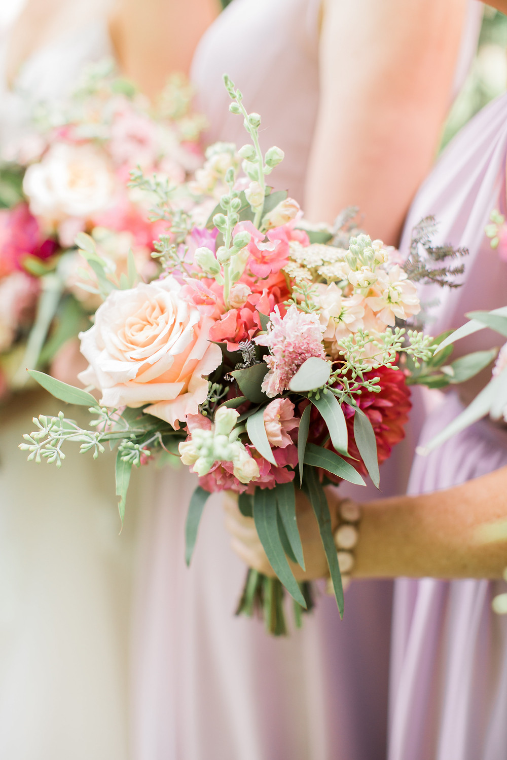 bridesmaid bouquets by studio bloom iowa with roses and dahlias in shades of coral and pink farm wedding