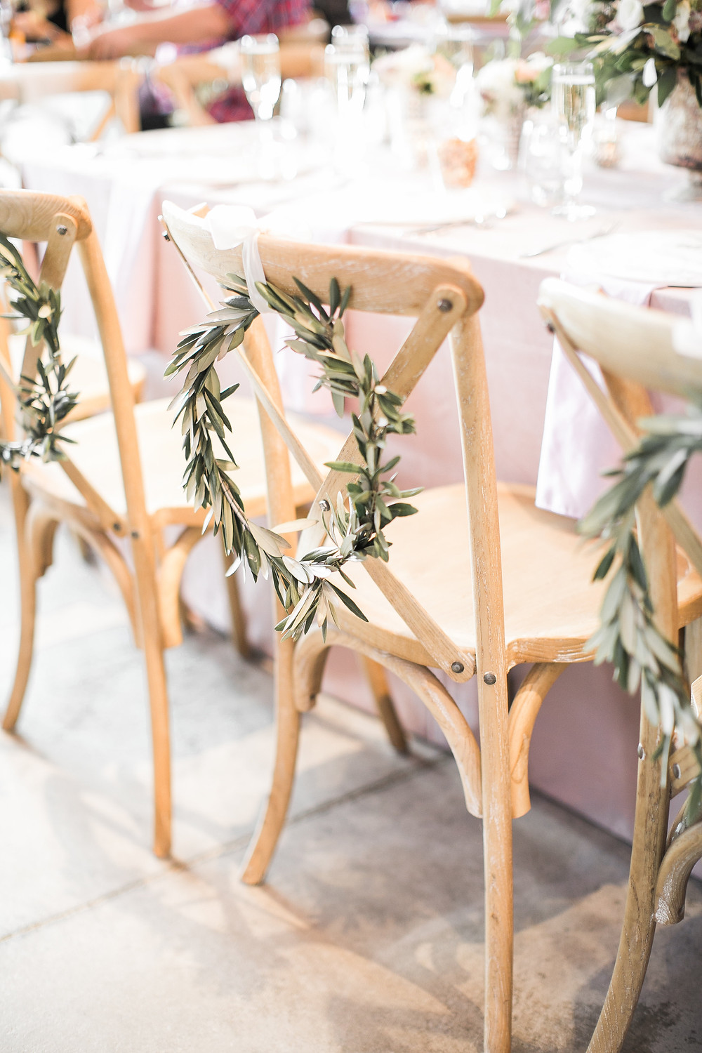 miniature olive wreath on wooden x back chair wedding head table with mauve velvet linen tablecloth