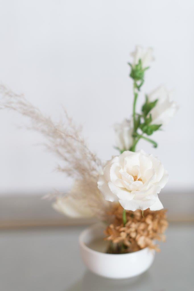 Minimalist neutral miniature arrangement with flower pin frog by Studio Bloom Iowa wedding florist of spray rose and pampas