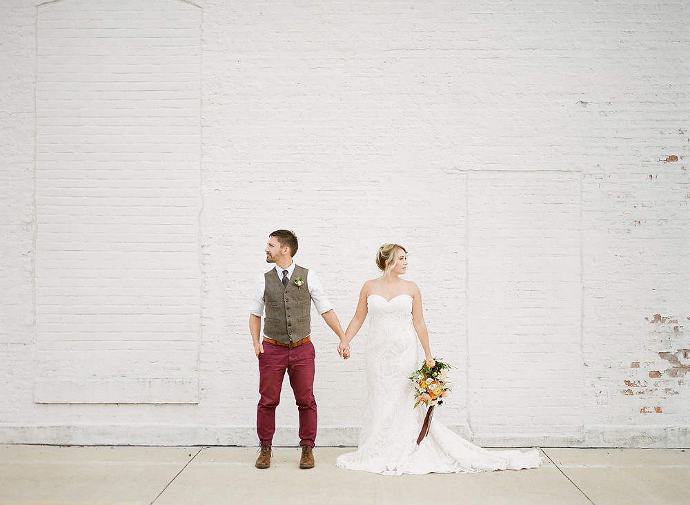 Bride and groom holding hands against white brick wall with peach and rust bridal bouquet of flowers by studio bloom iowa wedding florist