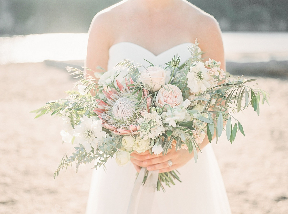 Bride at Palisades Kepler Park holding studio bloom iowa beach inspired bridal bouquet of king protea, roses, and olive