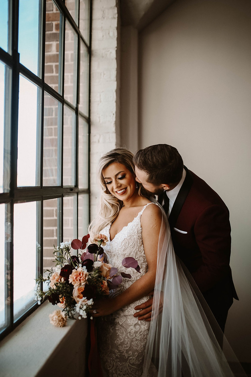 bride and groom with Studio Bloom Iowa bridal bouquet in burgundy and peach