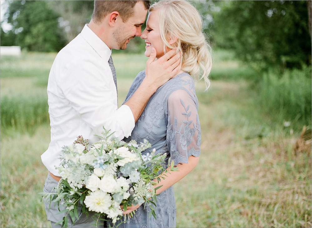 anniversary couple in field with Studio Bloom Iowa bridal bouquet in white and blue