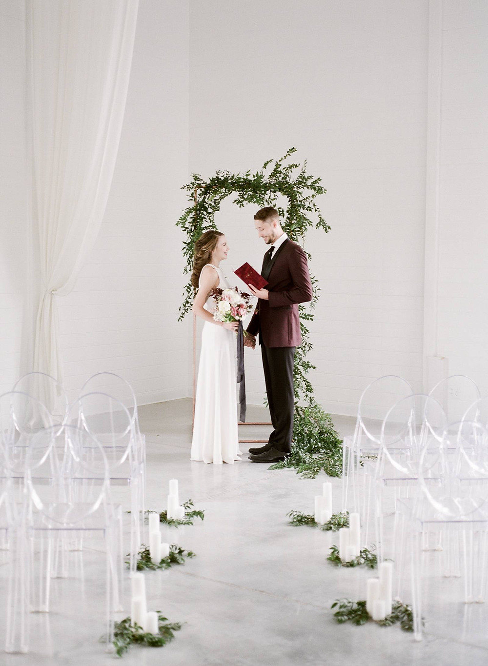 Bride and groom exchanging vows at Ashton Hill Farm with minimalist greenery arch by Studio Bloom Iowa wedding florist