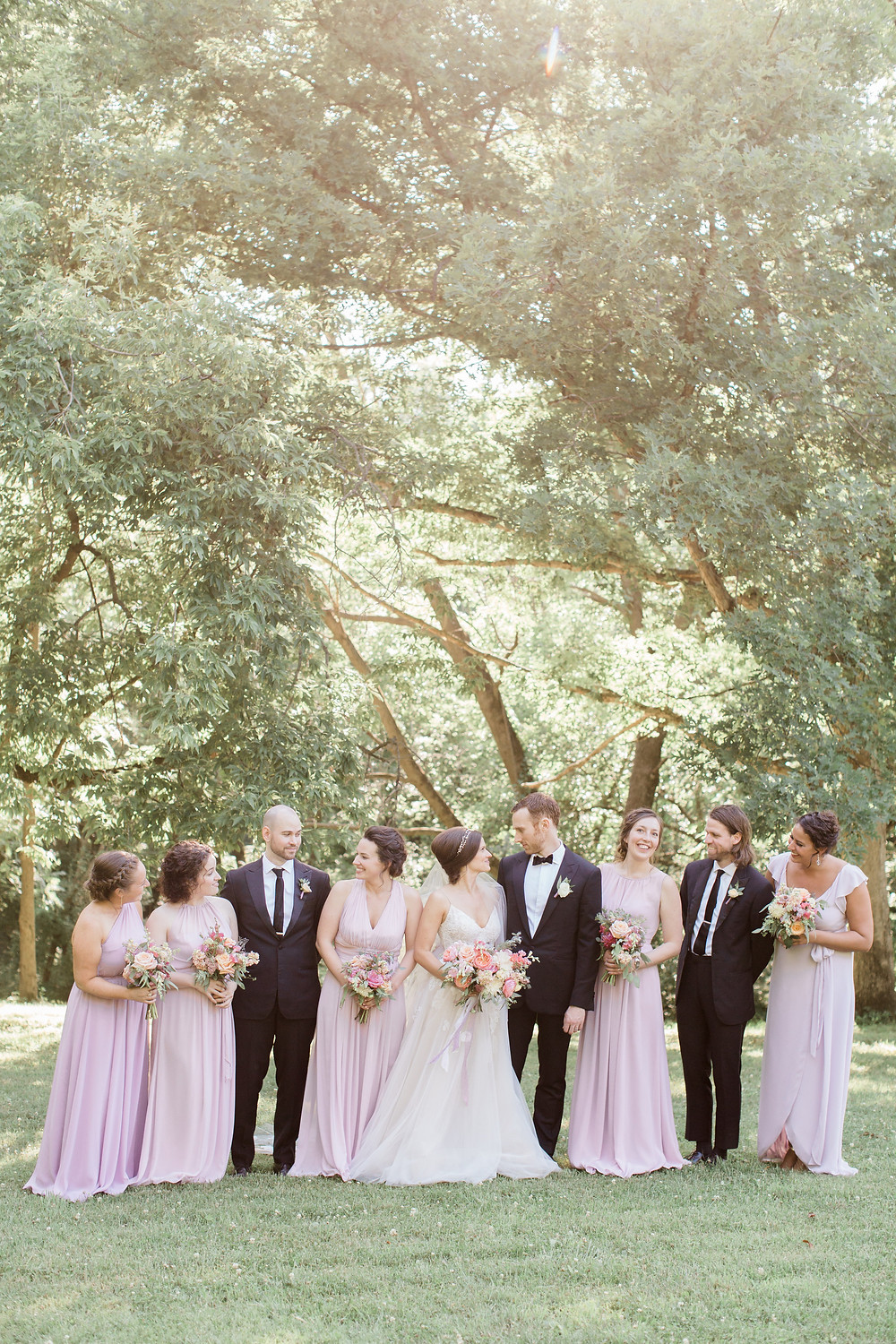Bridal party in lavender dresses and black suits with pastel summer garden wedding bouquets by studio bloom iowa