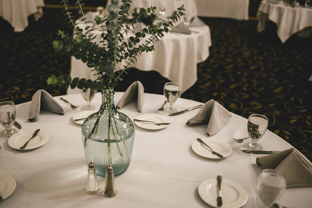 eucalyptus greenery in demijohn recycled glass bottle wedding reception centerpiece on white table cloth