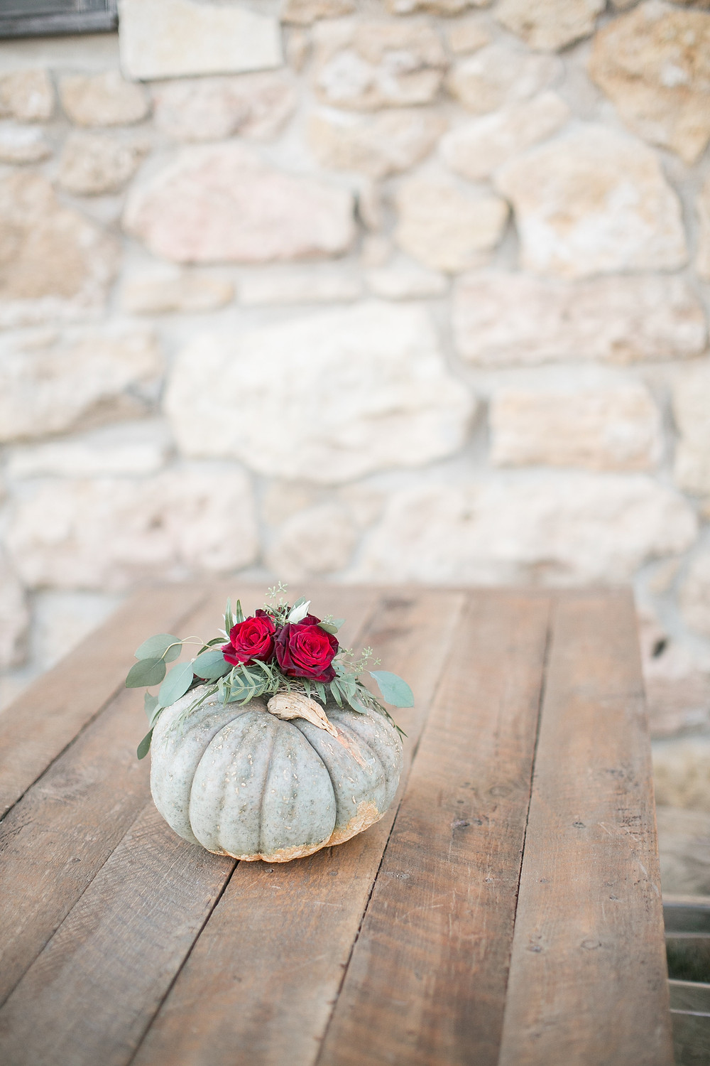 grey pumpkin with burgundy roses centerpiece on wood table by studio bloom iowa