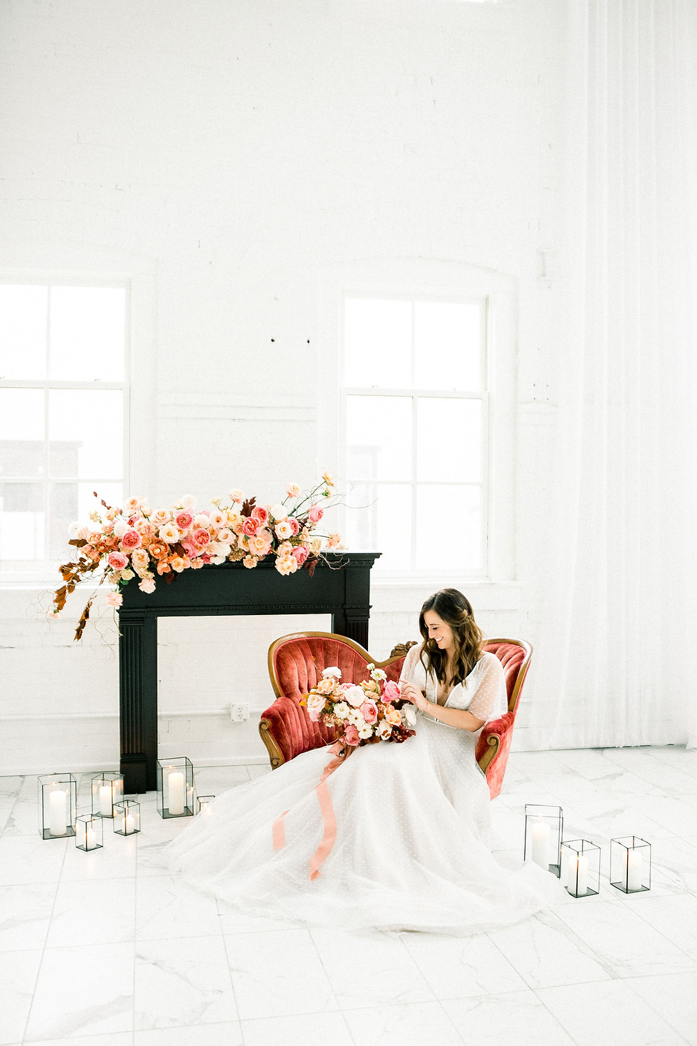 Bride on vintage settee next to black fireplace mantel with pink and peach flowers and bridal bouquet by Studio Bloom Iowa