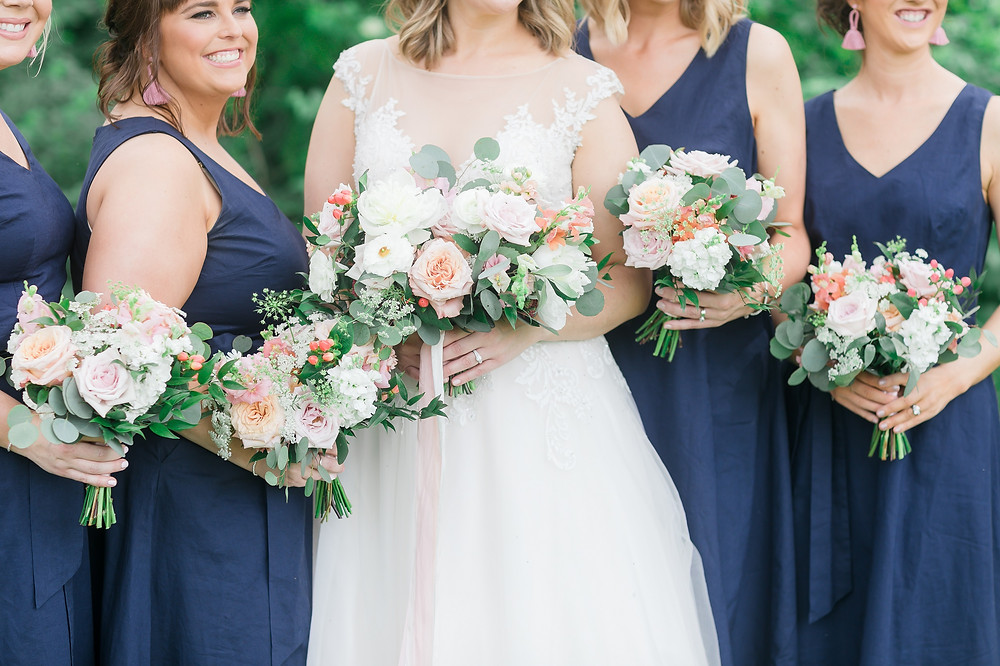 Summer wedding bouquets by Studio Bloom Iowa in shades of pink, peach, and white held by bride and bridesmaids in navy dresses