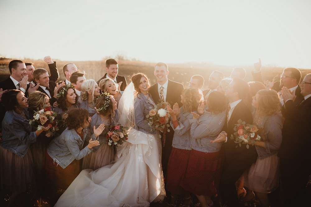 Bridal party wearing denim jackets cheering in field at sunset holding autumn flower bouquets by Studio Bloom Iowa wedding florist