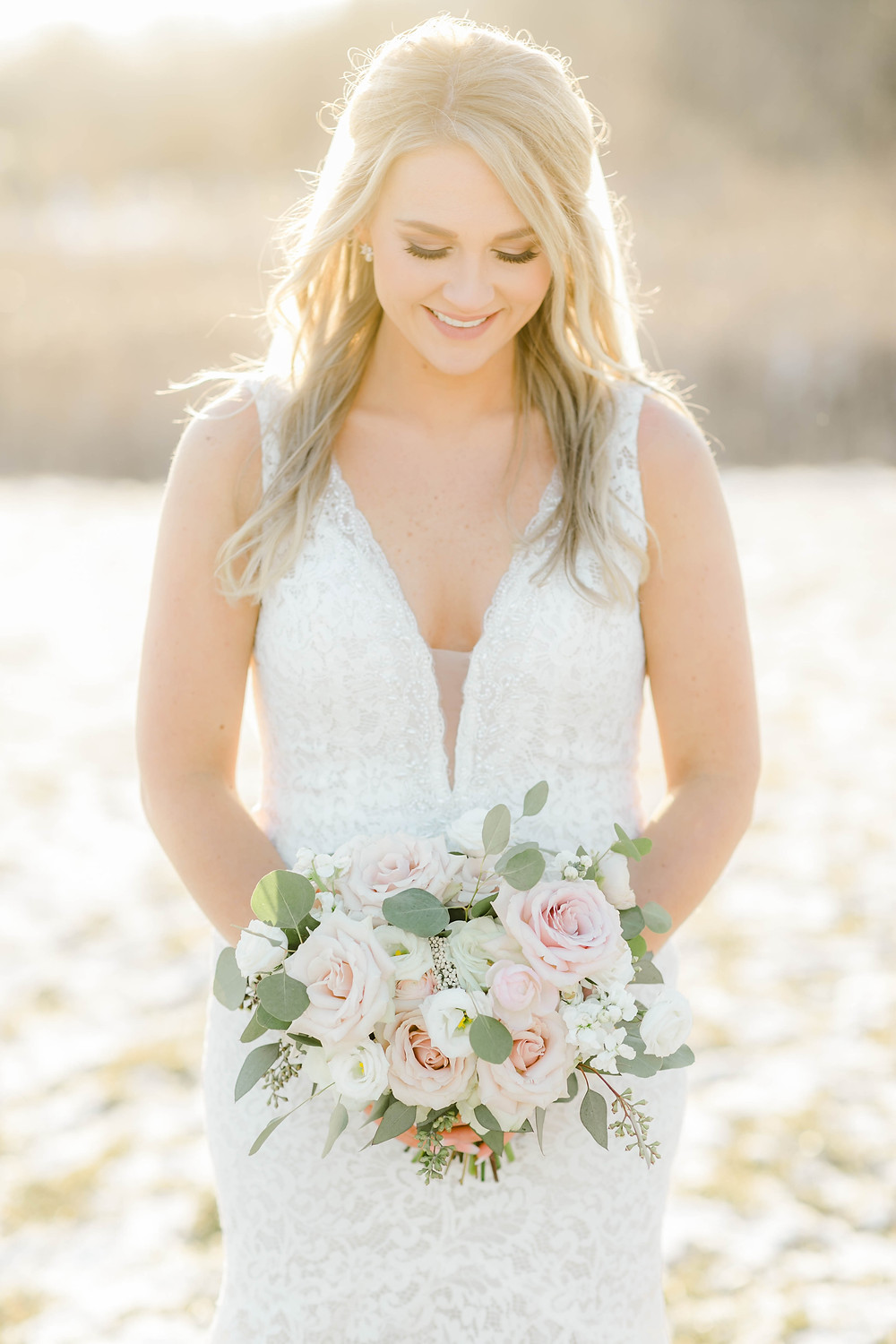 Bride with floral bouquet of blush roses, ranunculus, lisianthus, stock, rice flower, and eucalyptus by Studio Bloom Iowa