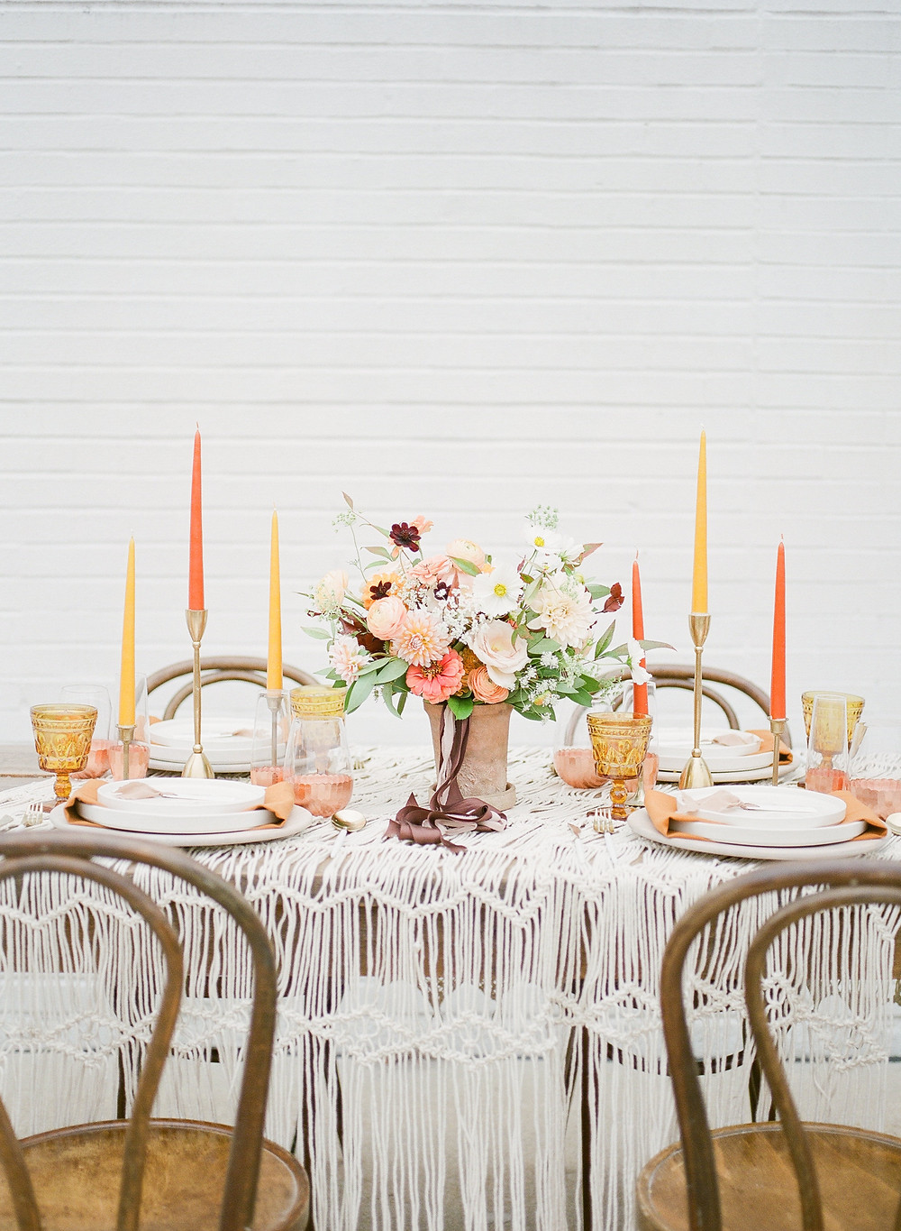 Boho wedding centerpiece by studio bloom iowa in terracotta pot with peach and brown summer flowers on a macramé table cloth
