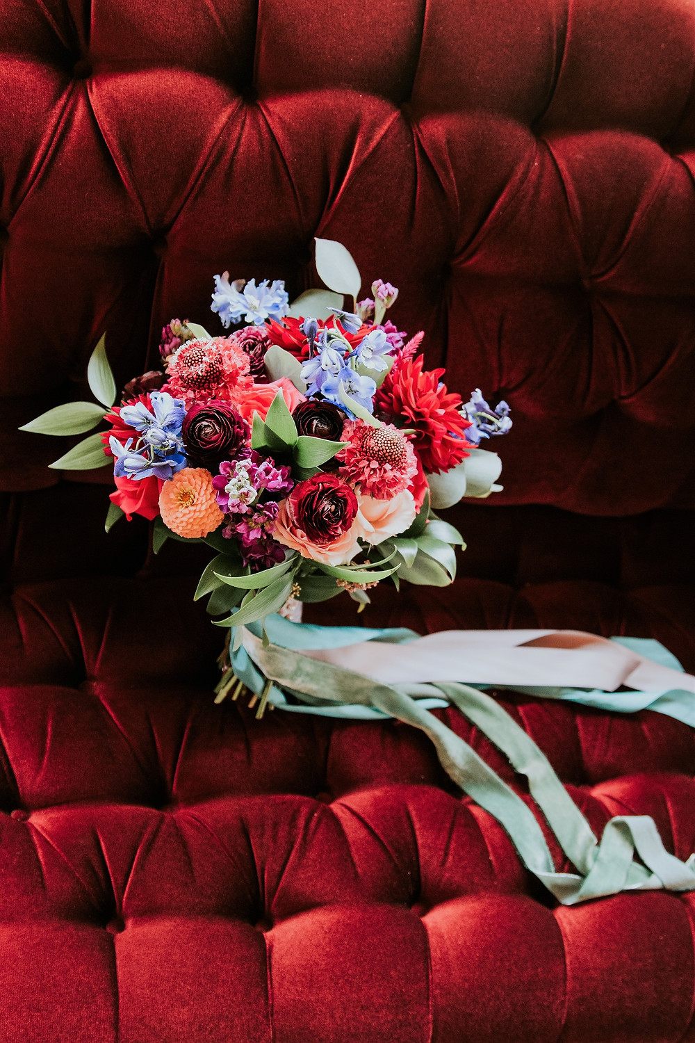 studio bloom iowa bright jeweltone bridal bouquet in reds, blues, purples, and peaches