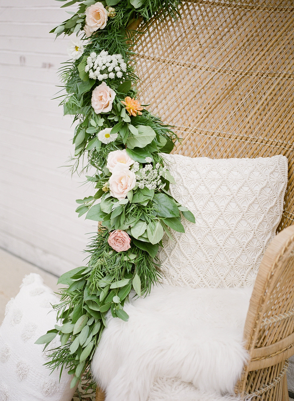 wicker peacock chair with macramé and faux fur pillows decorated with floral and greenery garland by studio bloom iowa