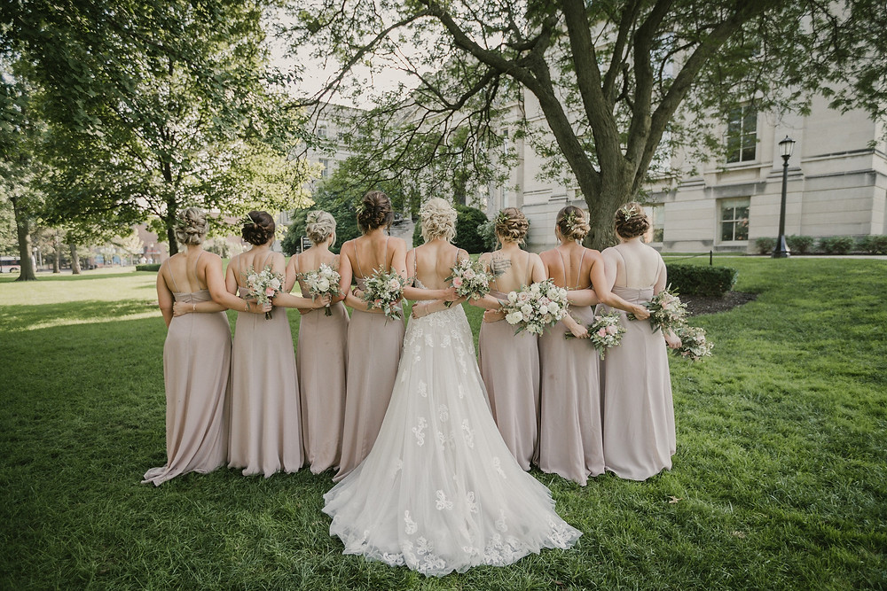 bride and bridesmaids in blush dresses holding bridal bouquets by studio bloom iowa with dahlias, roses, and eucalyptus