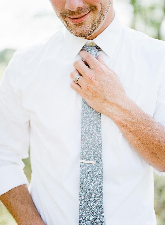 man straightening blue floral tie