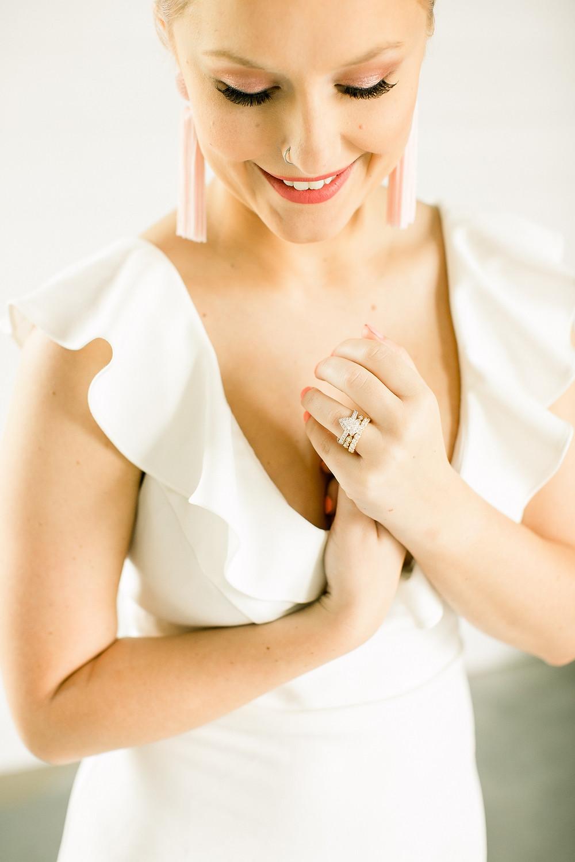 modern bride in ruffled dress with pink fringe earrings and teardrop wedding ring