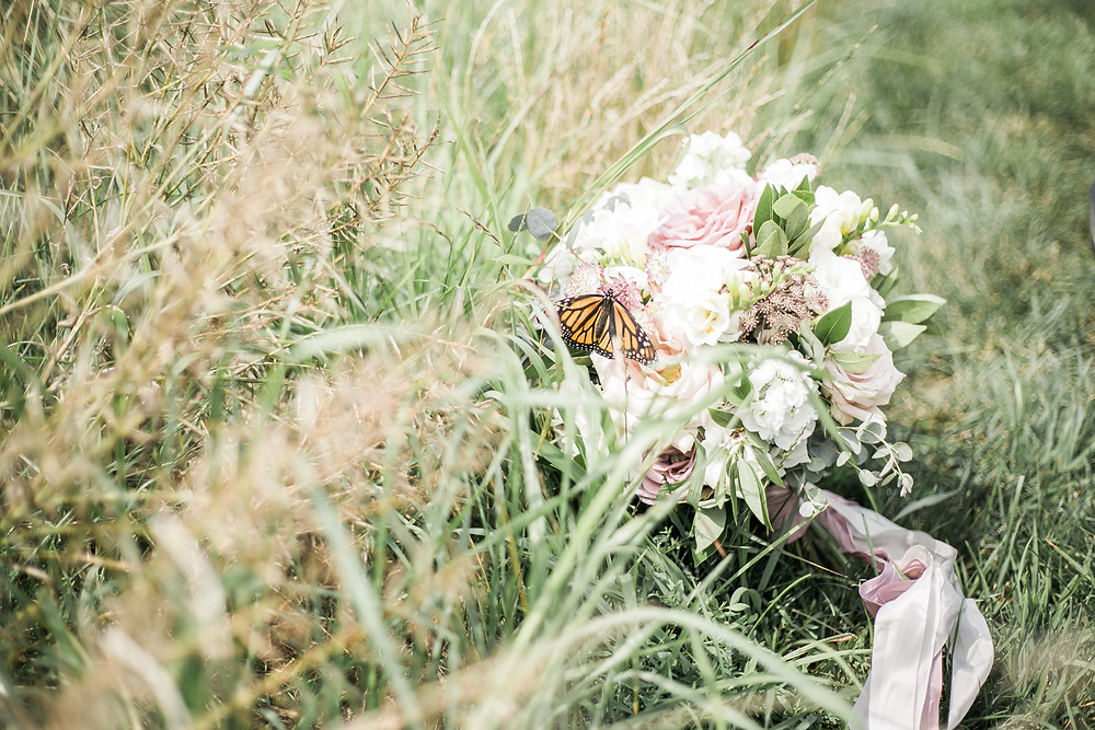 mauve and white bridal bouquet by studio bloom iowa wedding florist laying in field of grass with monarch butterfly