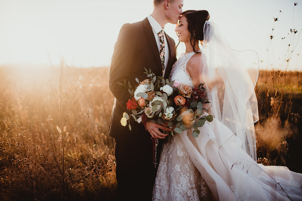 Studio Bloom Iowa fall earthtone bridal bouquet held by happy bride in full lace gown and groom in a field at sunset