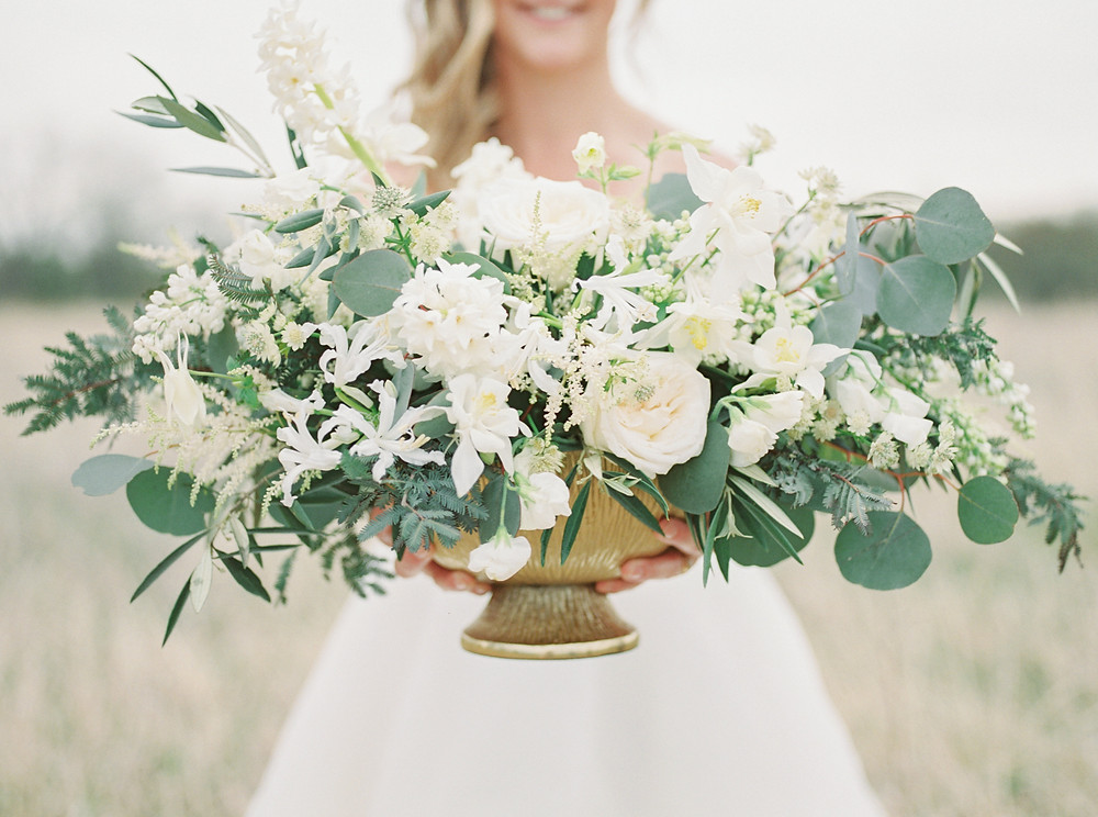 bride holding lush garden centerpiece in gold compote bowl by studio bloom iowa with garden roses, astilbe, olive, and eucalyptus