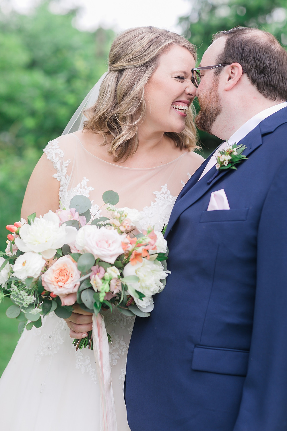 Bride and groom snuggling with garden bridal bouquet of peonies, roses, ranunculus, and eucalyptus by Studio Bloom Iowa