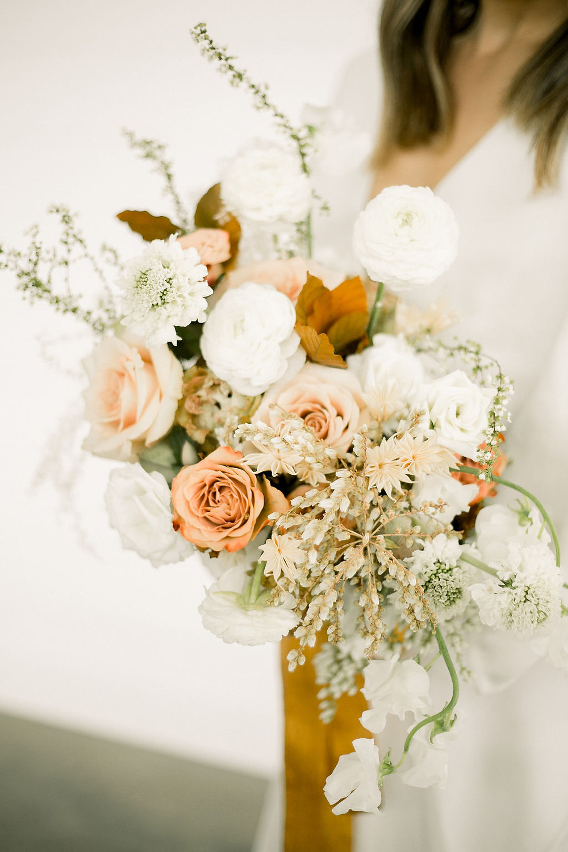 Studio Bloom Iowa minimalist bridal bouquet in neutral peach and copper of roses, ranunculus, sweet pea, spirea, and pieris