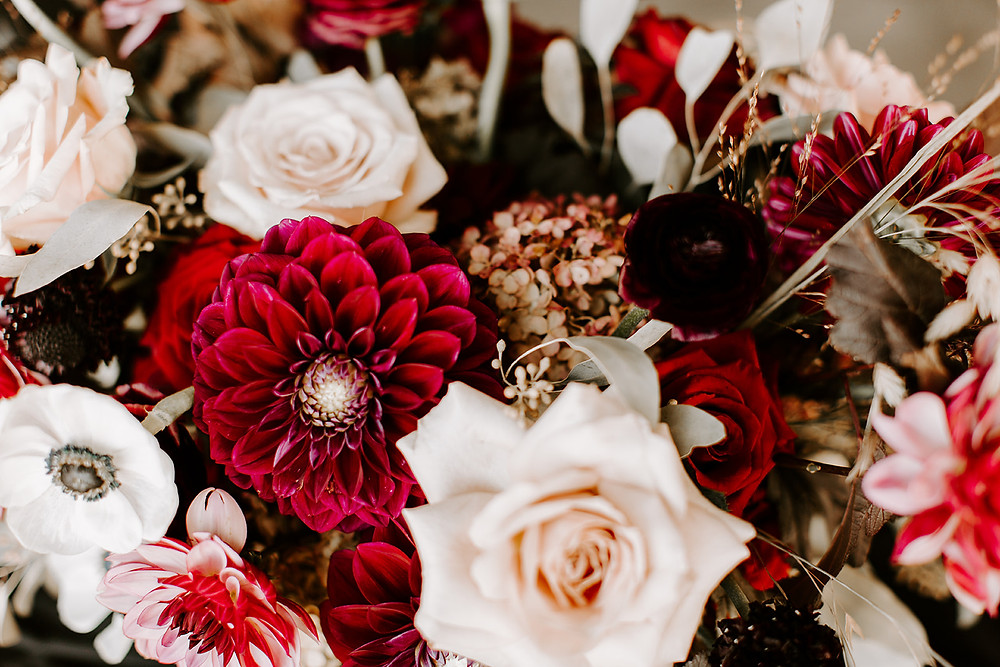 closeup of wedding flowers in rich tones of burgundy, red, and blush by Studio Bloom Iowa