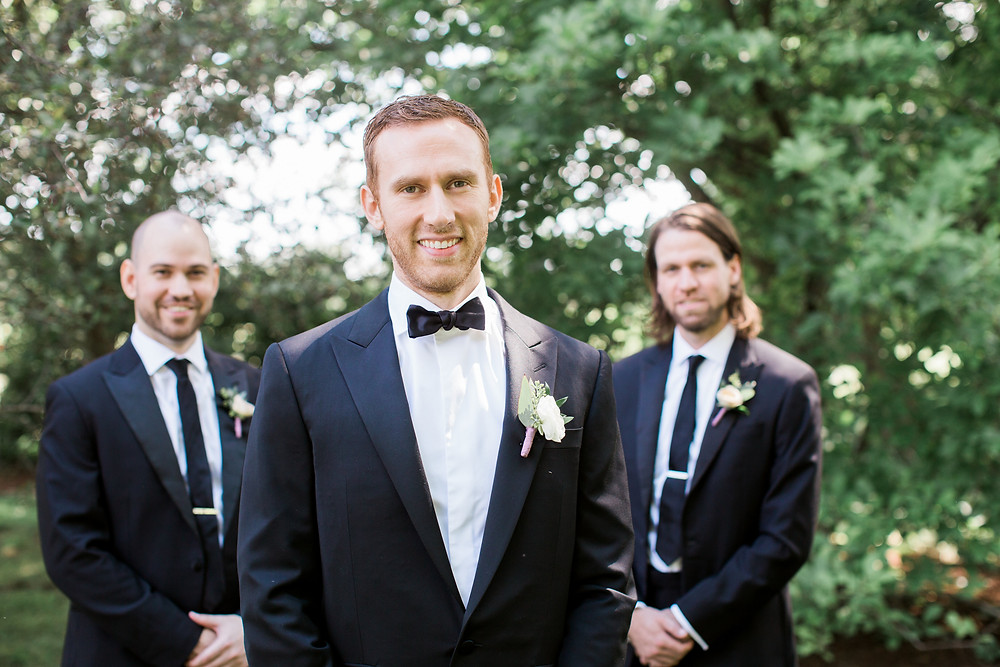 groom and groomsmen in black suits with ranunculus boutonnieres by studio bloom