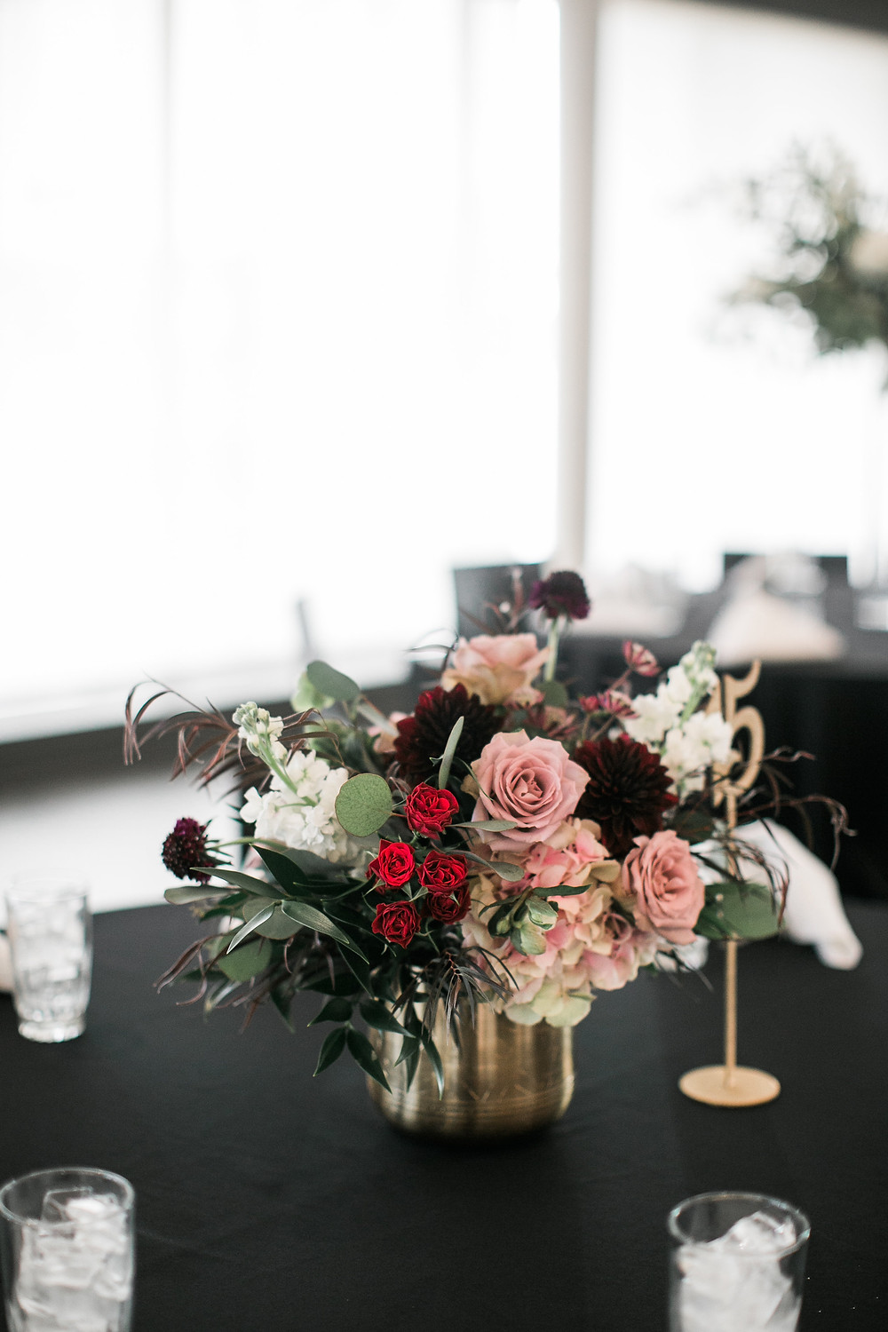 wedding reception centerpiece by studio bloom iowa with mauve roses, burgundy dahlias, stock, antique hydrangea in gold vase