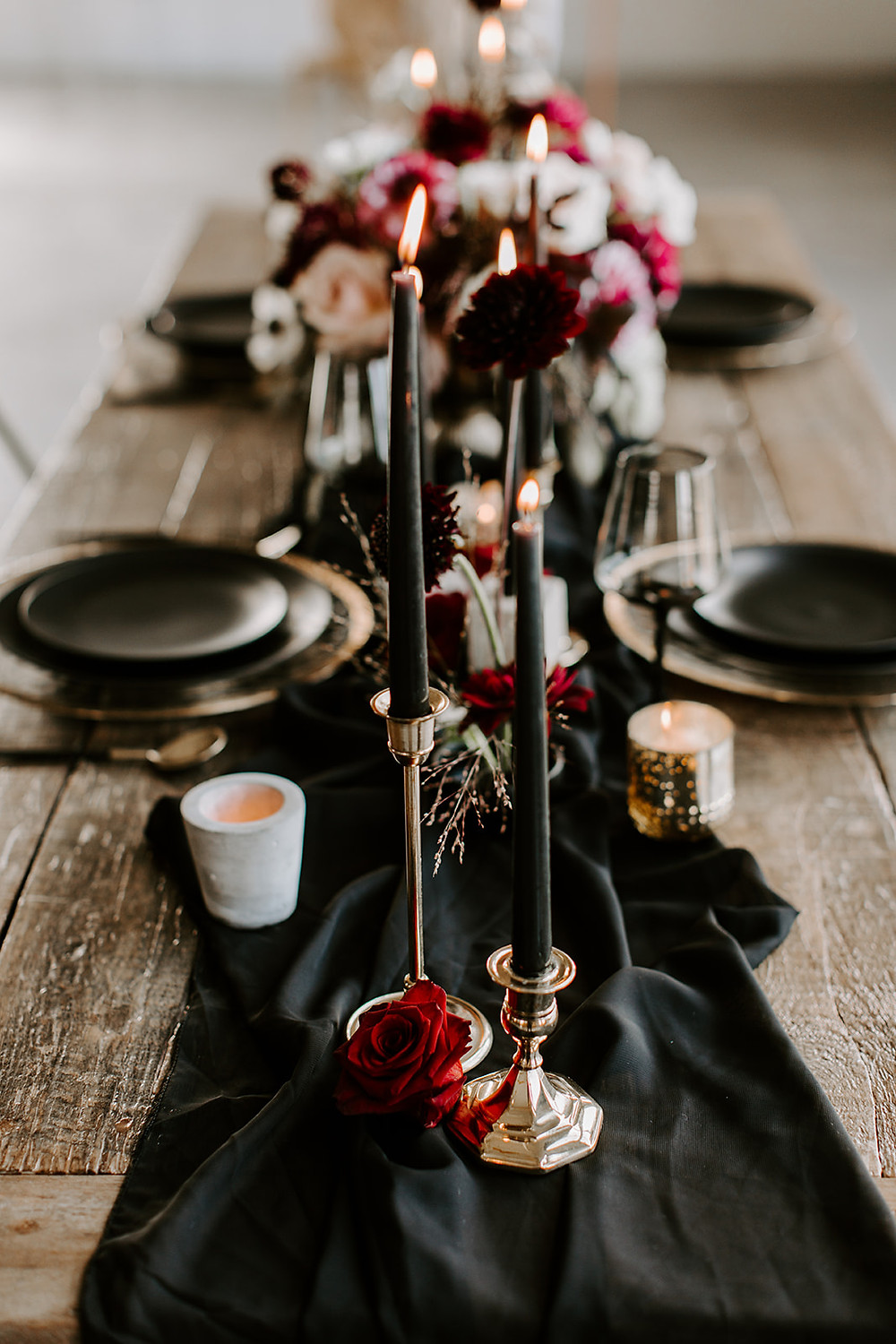 moody wedding reception tablescape with black taper candles and red roses