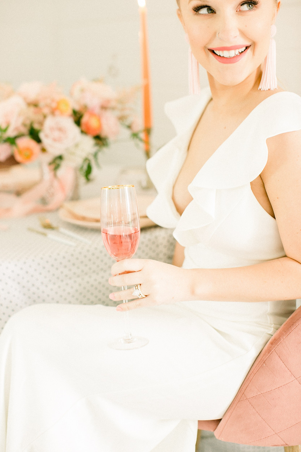 Smiling bride in ruffled dress holding wine at table with polka dot linens and blush and peach flowers by Studio Bloom Iowa