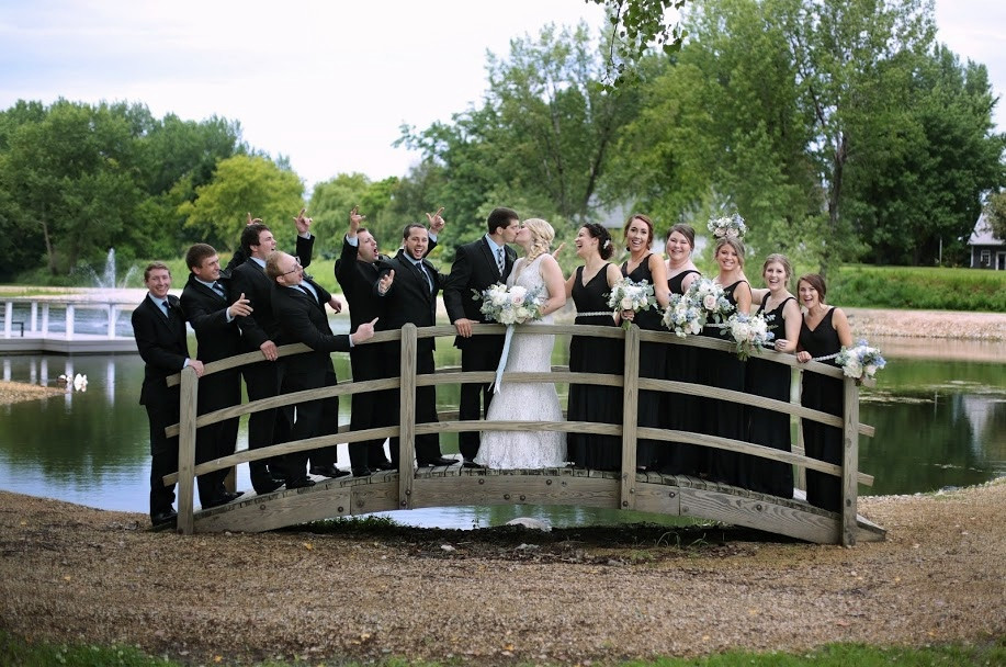 bridal party in black suits and dresses on bridge at pond in New Hampton, Iowa