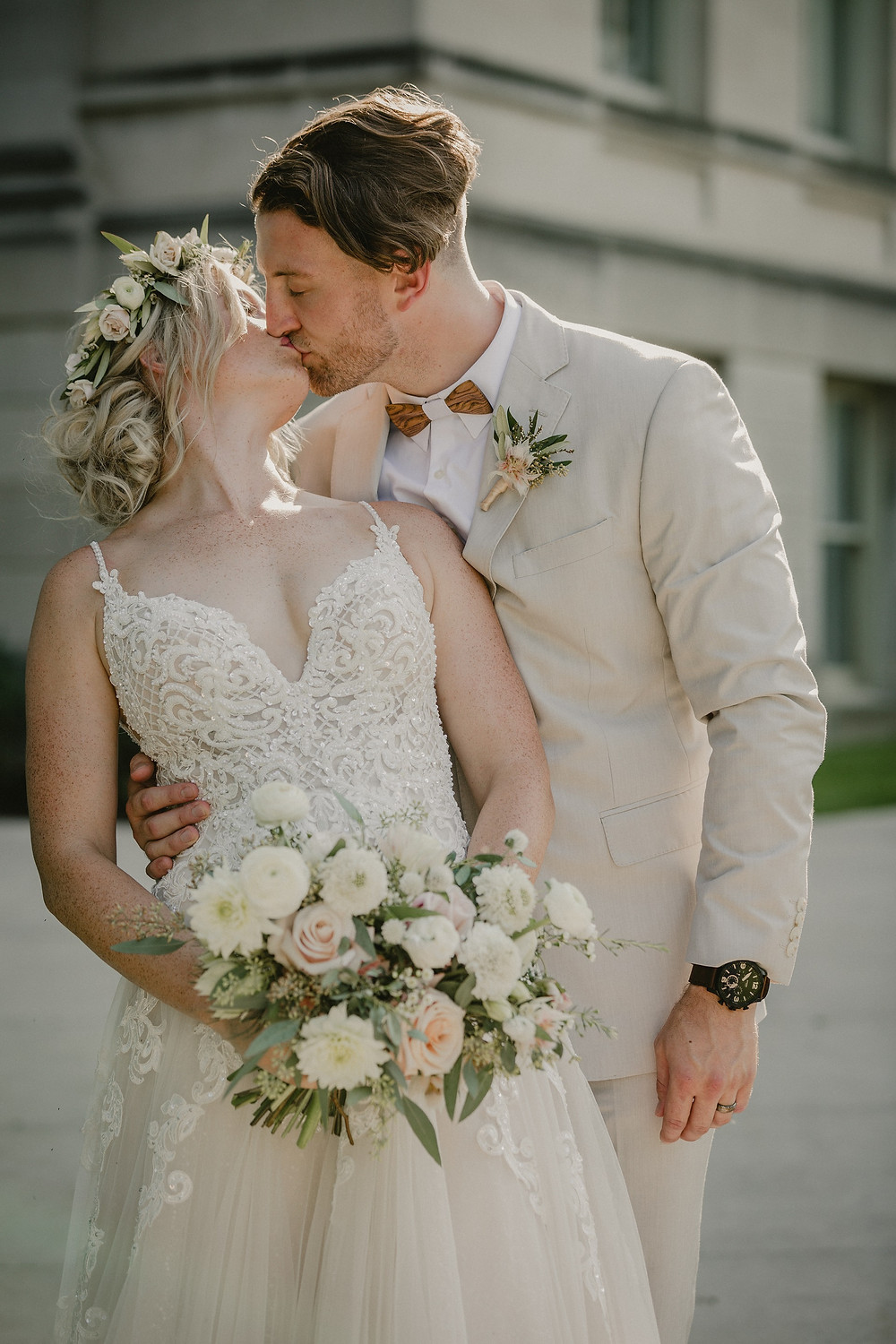 bride and groom kissing holding blush and white bridal bouquet by studio bloom iowa wedding florist