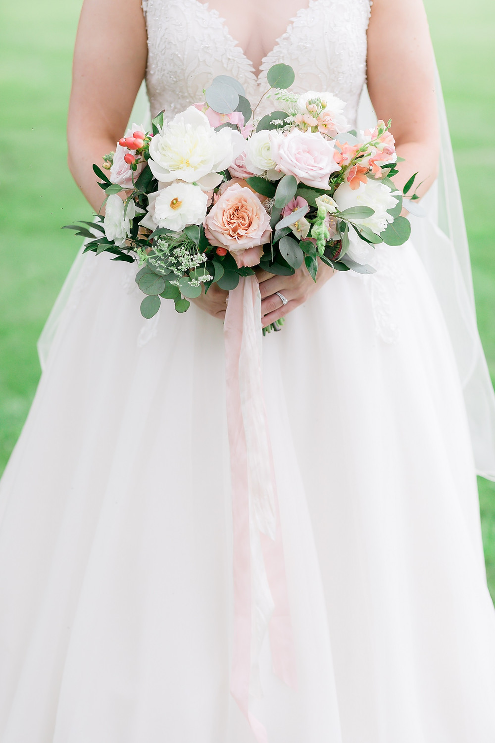 Bride holding Studio Bloom Iowa bridal bouquet in pink, peach, and white with peonies, roses, snapdragons, ranunculus, berries