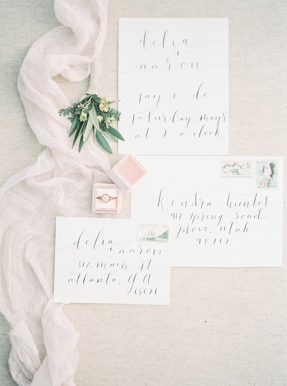 calligraphy invitation suite with olive greenery boutonniere and wedding ring