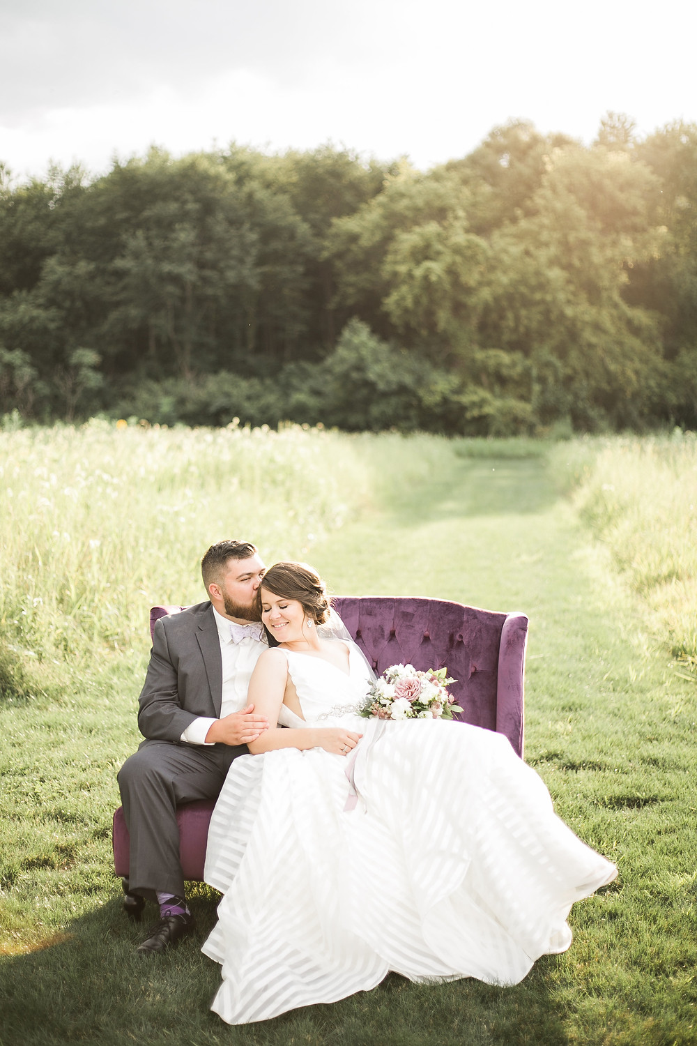 bride and groom cuddling on a purple velvet couch in a field of grass at sunset
