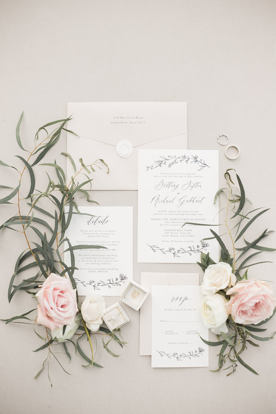 calligraphy invitation suite with rings in a mrs box and flowers and eucalyptus