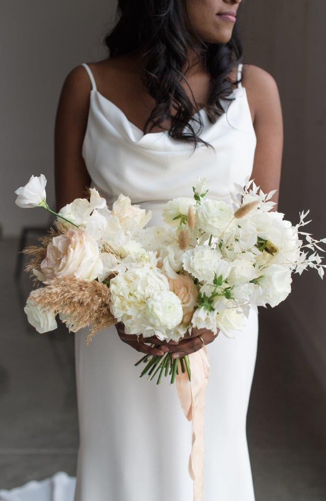 Fine art white bridal bouquet by Studio Bloom Iowa wedding designer with garden roses, peonies, ranunculus, and pampas