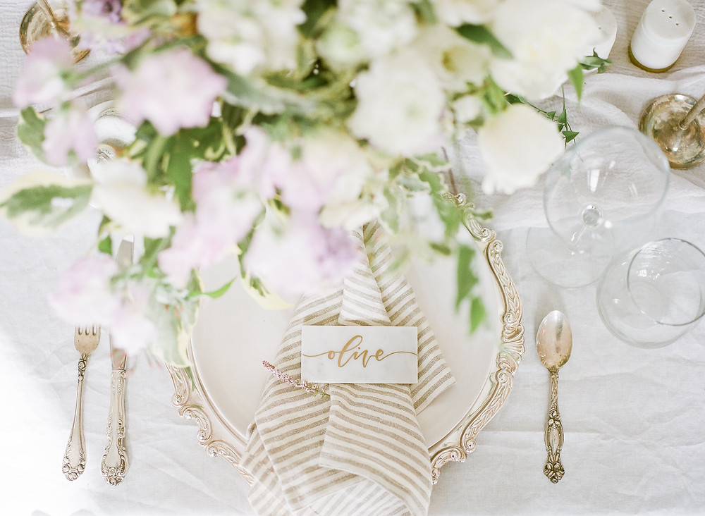 wedding dinner plate with marble name card, silverware, and lavender and white flowers