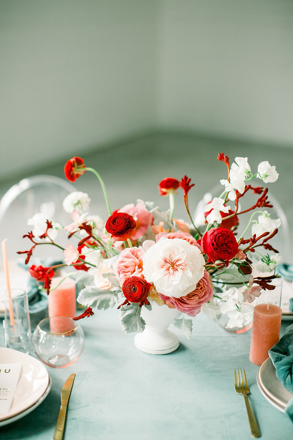 Modern centerpiece by Studio Bloom Iowa wedding florist in red, blush, and teal with garden roses, ranunculus, and sweet pea