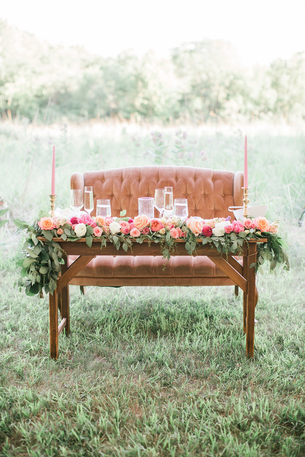 wedding sweetheart table with peach vintage couch and pink flower garland by studio bloom iowa florist