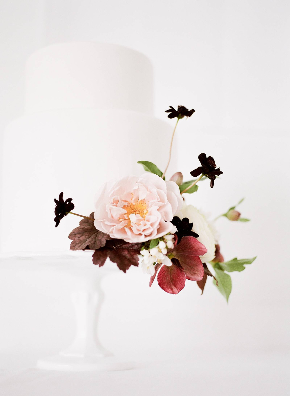 Minimalist white wedding cake on white stand with mauve and burgundy flowers