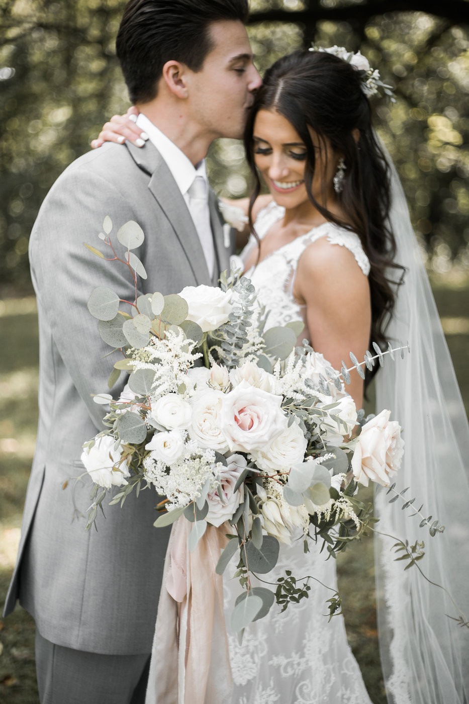 bride holding large blush white and eucalyptus bouquet by studio bloom iowa while groom is kissing her head in grey suit