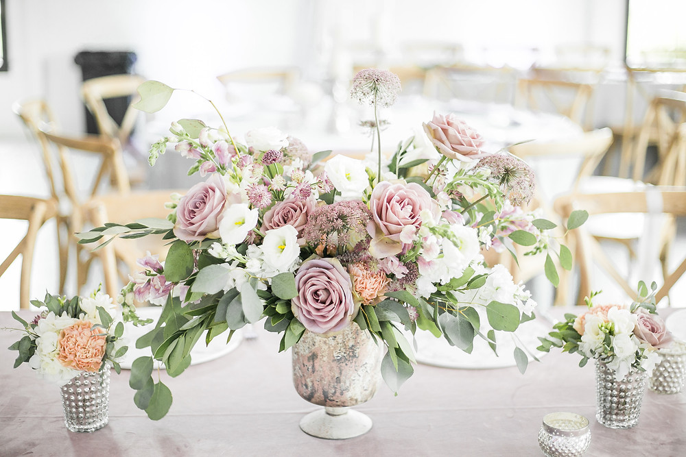 lush floral wedding centerpiece  by studio bloom iowa of mauve roses, eucalyptus, white lisianthus and queen annes lace