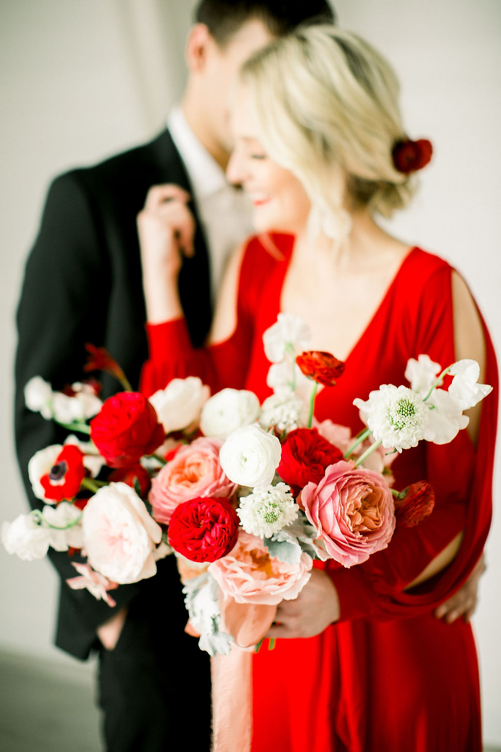 Bride in red dress and groom holding modern blush and red bouquet by Studio Bloom Iowa with roses, ranunculus, and sweet pea