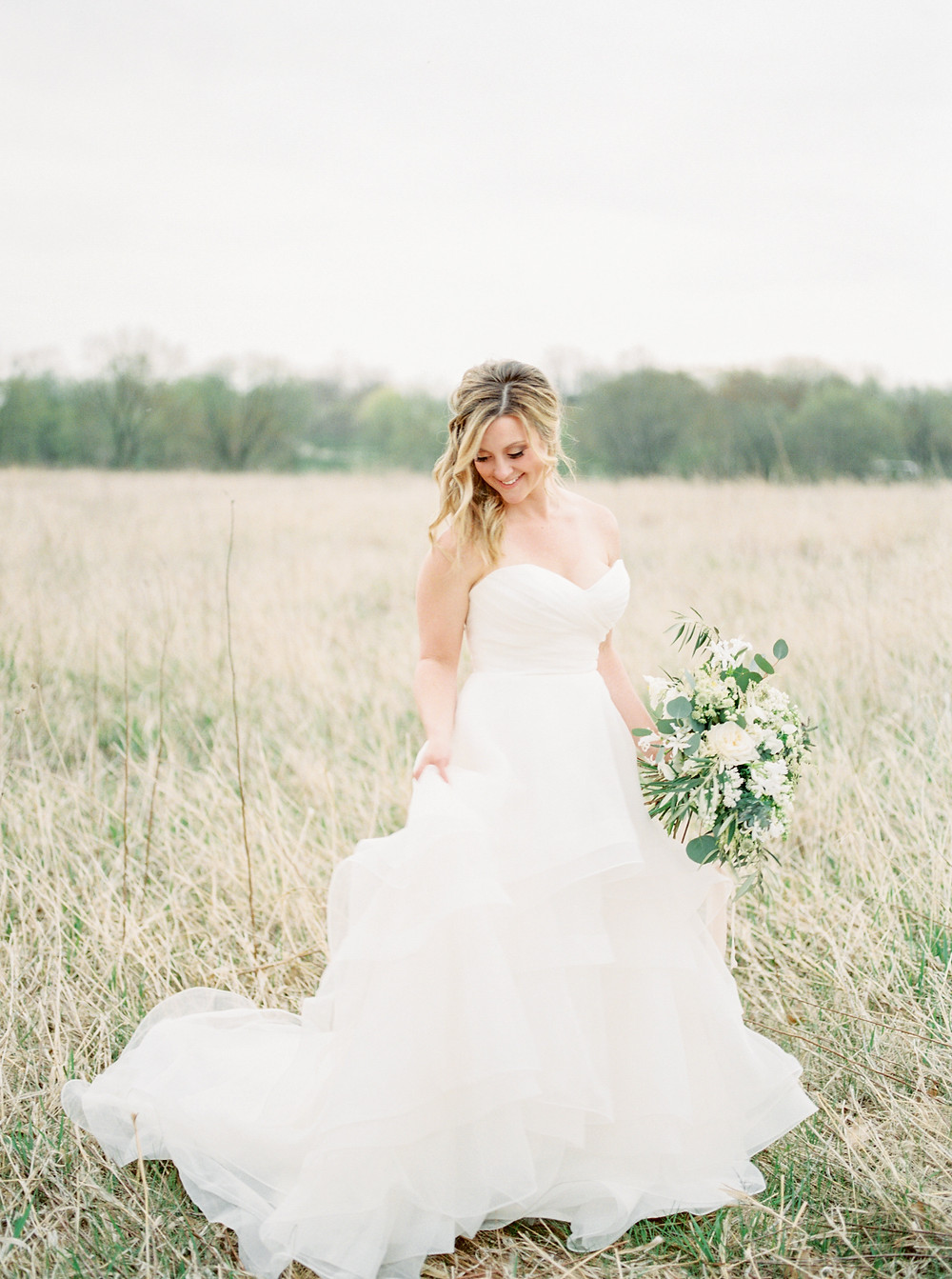bride in a prairie holding bridal bouquet in white and green by studio bloom iowa floral designer