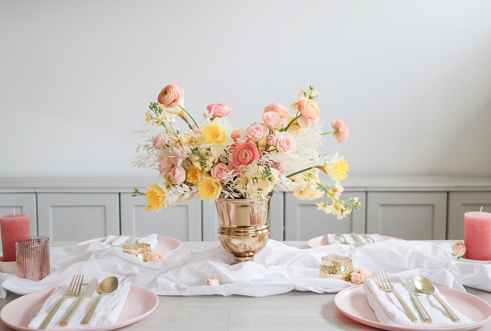 spring table centerpiece by Studio Bloom Iowa of daffodils, spray roses, ranunculus, and stock