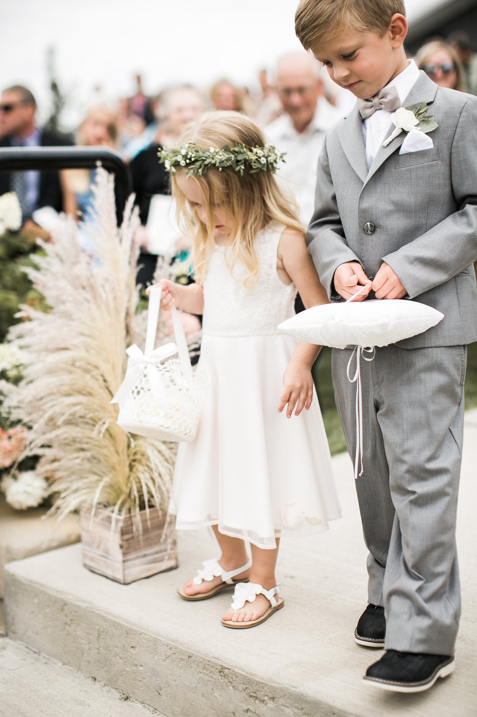 flower girl and ringbearer walking down aisle with pampas grass at ashton hill